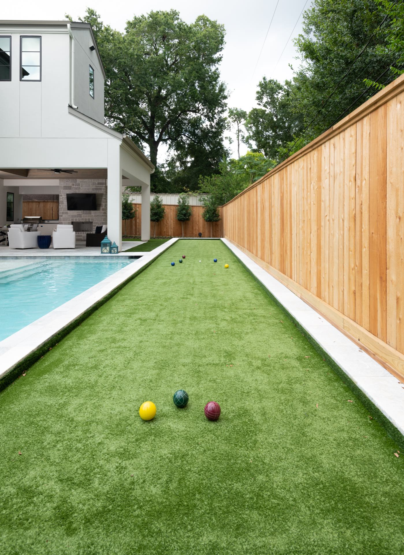 A bocci game is set up next to an Avea custom pool.