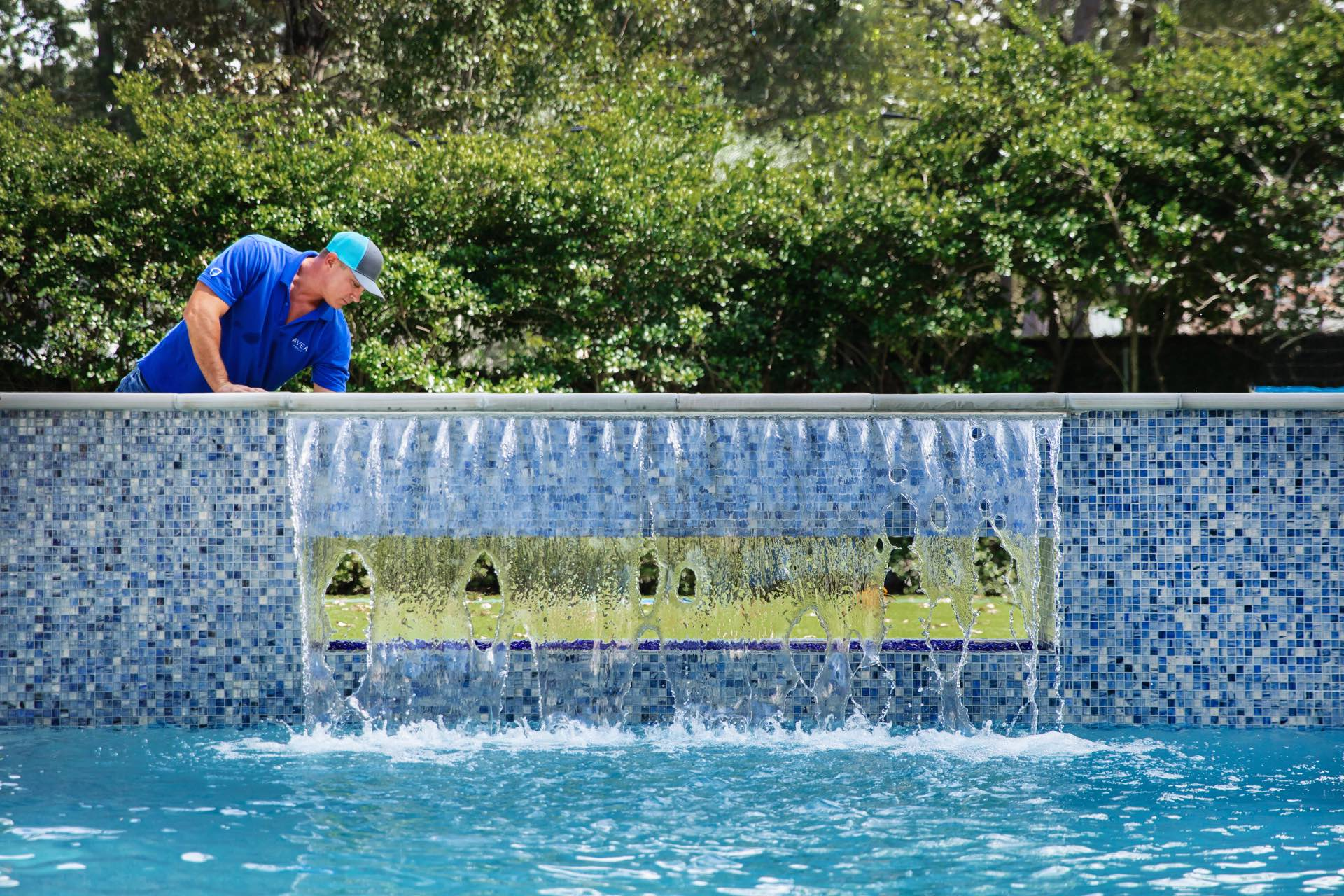 A maintenance worker cleans the outside of an Avea pool.