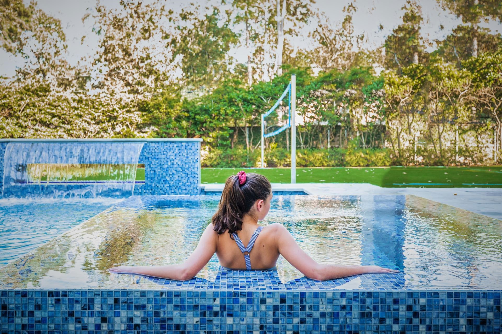 Woman relaxing in an AVEA custom swimming pool