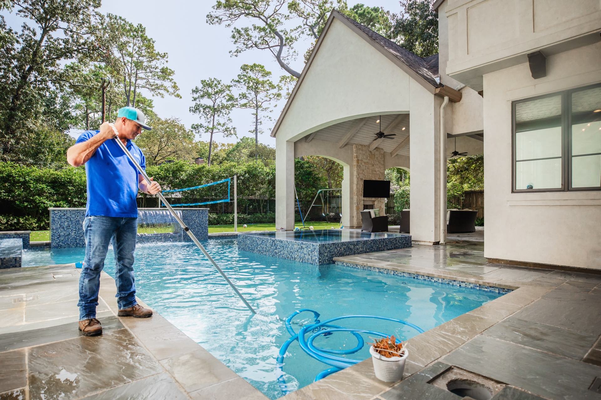 Maintenance worker cleans leaves from Avea pool.